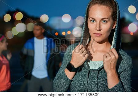 Flash photography portrait of trendy blond hipster woman wearing a smartwatch and planning her workout on an app ready for night jogging with her running group in an urban background with bokeh lights.
