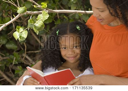 African American mother and her daugher reading together.