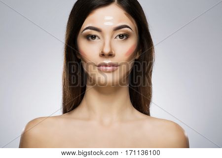Model with contour and highlight makeup. Contouring face make-up applying sample. Beauty portrait, head and shoulders, full face. Indoor, studio