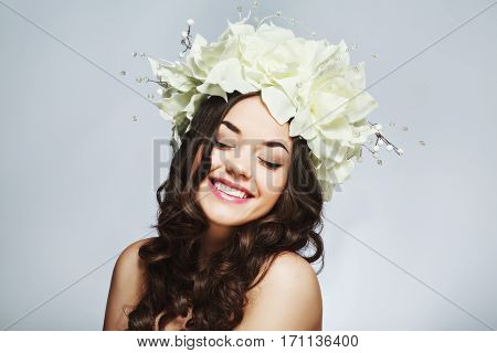 Attractive girl with dark curly hair, big eyes, dark eyebrows and naked shoulders, closed eyes, wearing big white wreath with flowers and smiling, beauty photo.
