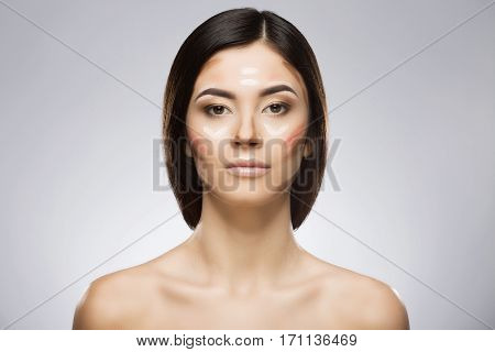 Model with professional contour and highlight face makeup applying sample. Hair at the back. Beauty portrait, head and shoulders, full face. Indoor, studio
