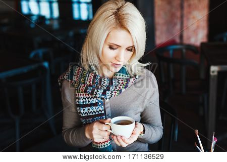 Cute blonde girl with nude make up wearing gray blouse and scarf, sitting in cafe with cup of coffee, copy space, portrait.