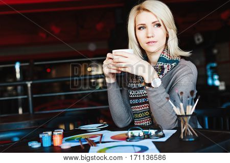 Beautiful blonde girl with nude make up wearing gray blouse and scarf, sitting in cafe with cup of coffee, paints and brushes on table, copy space, portrait.