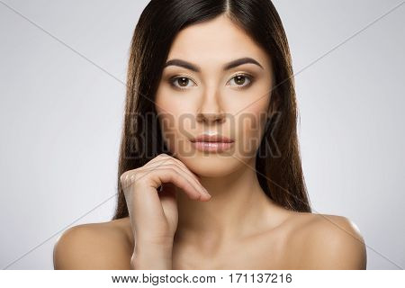 Beautiful girl with nice make-up looking at camera and holding her hand under chin. Beauty portrait, closeup, head and shoulders. Indoor, studio, gray background