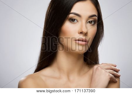 Beautiful girl with nice make-up looking at camera and holding her hand on shoulder. Beauty portrait, head and shoulders. Indoor, studio, gray background