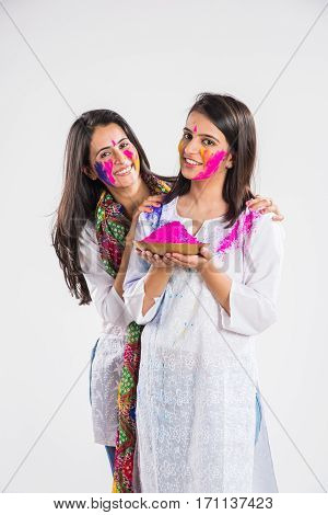 two beautiful indian girls holding colours and sweets or pichkari on Holi festival, standing isolated over white background with copy space