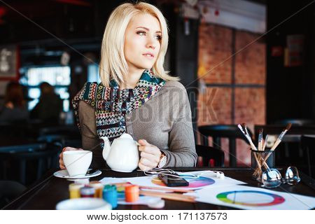 Beautiful blonde girl with nude make up wearing gray blouse and scarf, sitting in cafe with cup of tea, paints and brushes on table, copy space, portrait.