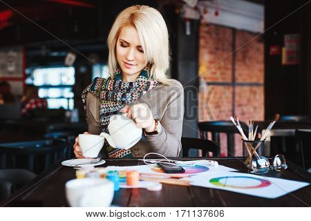 Cute blonde girl with nude make up wearing gray blouse and scarf, sitting in cafe with cup of tea, paints and brushes on table, copy space, portrait.