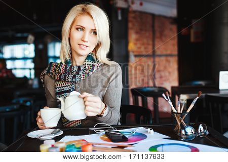 Attractive blonde girl with nude make up wearing gray blouse and scarf, sitting in cafe with cup of tea, paints and brushes on table, copy space, portrait.