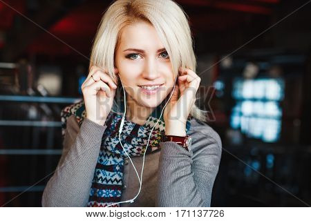Beautiful blonde girl with nude make up wearing gray blouse and scarf, wearing headphones and smiling, copy space.
