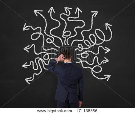 Businessman thinking a solution drawing on chalkboard