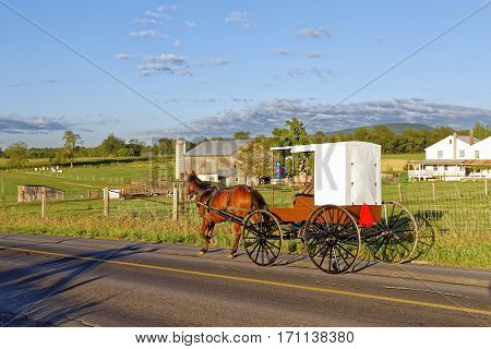 An Amish horse and carriage travels on a rural road in Mifflin County Pennsylvania USA.