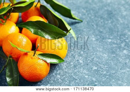 Fresh tangerines with leaves copy space closeup