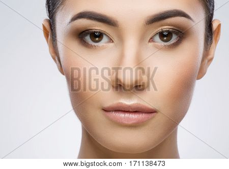 Model with nude make-up looking at camera. Beauty portrait, closeup, full face. Indoor, studio, gray background