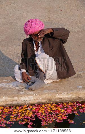 PUSHKAR, INDIA - FEBRUARY 17: A Hindu man offers prayers at the holy lakeside, Pushkar Sarovara, Hindu pilgrimage site, Rajasthan, India on February 17, 2016.