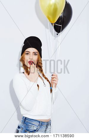 Funny red-haired girl with long hair wearing white shirt and black hat holding balloons and acting surprised, stylish haircut and makeup, portrait.