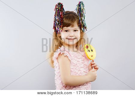 Lovely little girl wearing pink dress, festoon ears and holding candy, looking at camera, gray studio background, copy space, portrait, smiling.