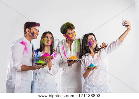 four indian friends or family taking selfie picture with smartphone or mobile on holy with faces painted and sweets and and Gulal colours in plate, isolated over white background with copy space