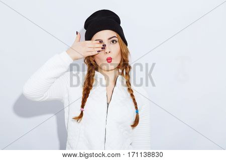 Young teenage red-haired girl with long hair wearing white shirt and black hat, stylish haircut and makeup, red lips, pathos emotion, posing.