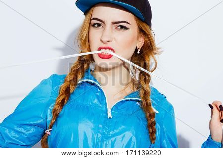 Beautiful teenage red-haired girl with long hair wearing blue jacket and black hat gnawing white rope, red lips, black manicure, portrait, emotions.