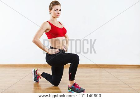 Thin sportive girl wearing snickers, black leggings and red short top doing squatting at gym holding hands on waist, fitness, white wall and wooden floor at background.