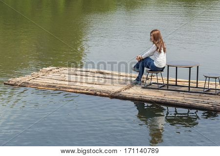 Woman sitting on a bamboo raft in the river