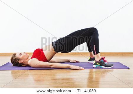 Thin sportive girl wearing snickers, black leggings and red short top doing push up on purple matt, fitness, white wall and wooden floor at background.