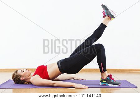 Cute sportive girl wearing snickers, black leggings and red short top doing leg raise on purple matt at gym, fitness, white wall and wooden floor, copy space.