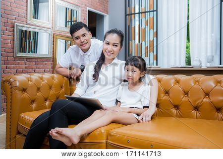 Mother father and doughter play tablet with wifi internet in vintage family room. Family and techology concept