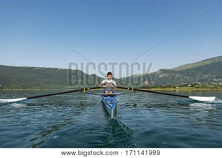 The young sportsman is rowing on the racing kayak.