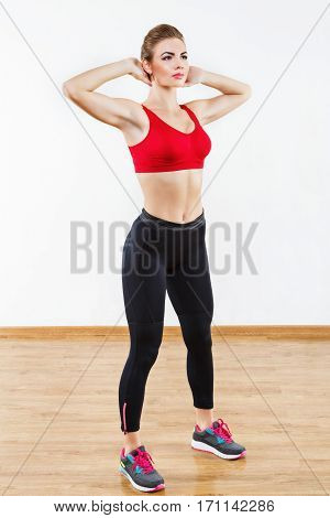 Cute sportive girl wearing snickers, black leggings and red short top standing at gym holding hands behind head, fitness, white wall and wooden floor at background.