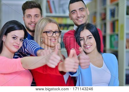 Cheerful group of students smiling at camera with thumbs up, success and learning concept.