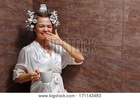 Young attractive housewife in the bathroom. Girl in a bathrobe and curlers drinking morning coffee. Good morning. Hot drink