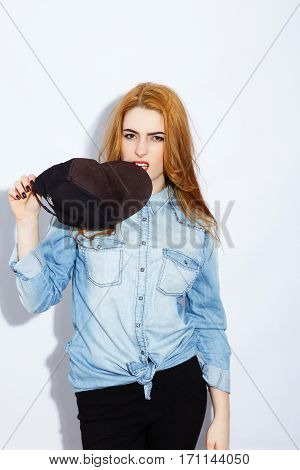 Angry posing, teenage red-haired girl with long hair wearing blue shirt and biting black hat, red lips, black manicure, portrait, copy space.