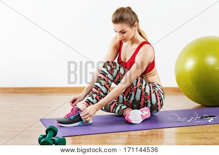 Beautiful with light brown hair wearing gray snickers, colorful leggings and red short top sitting on purple matt at gym, fitness, white wall and wooden floor.