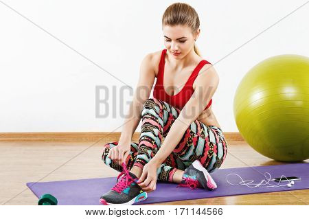 Cute with light brown hair wearing gray snickers, colorful leggings and red short top sitting on purple matt at gym with mobile phone and fitball, fitness.