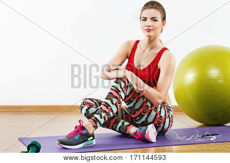 Nice with light brown hair wearing gray snickers, colorful leggings and red short top sitting on purple matt at gym with mobile phone and fitball, fitness, portrait.
