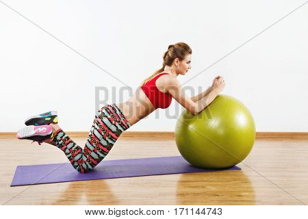 Attractive girl with light brown hair wearing gray snickers, colorful leggings and red short top doing exercises with fitball on purple matt at gym, fitness.