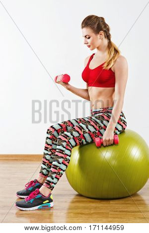 Nice  girl with light brown hair wearing gray snickers, colorful leggings and red short top sitting on fitball at gym, holding pink dumbbells, fitness.