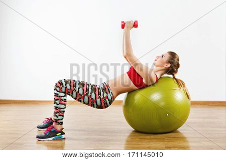 Lovely girl with light brown hair wearing gray snickers, colorful leggings and red short top doing exercises with fitball at gym, holding pink dumbbells.