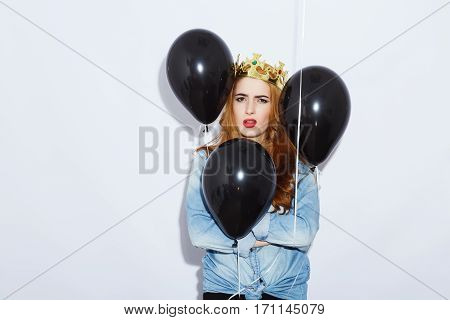 Lovely teenage red-haired girl with long hair wearing blue shirt and crown holding balloons, red lips, black manicure, copy space, annoyed posing.