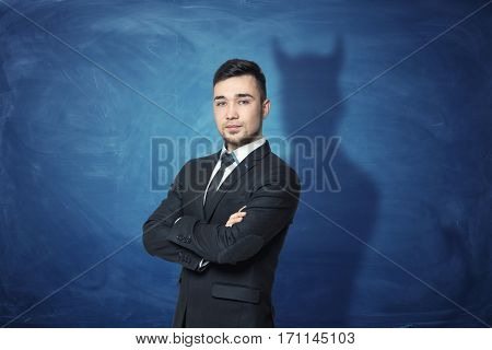 Businessman on blue chalkboard background with his shadow having devil horns. Business and competition. Workplace communication. Showing true colors.