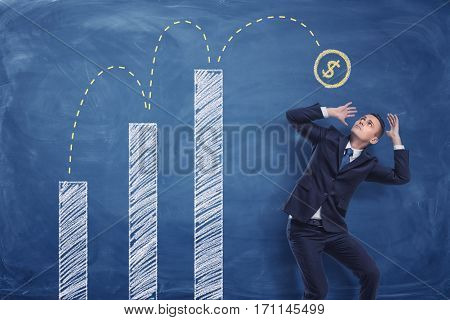 Businessman cowering on blue blackboard background with chalk drawing of a coin bouncing up from white graphs to man's head. Business statistics. Calculating money. Business management.