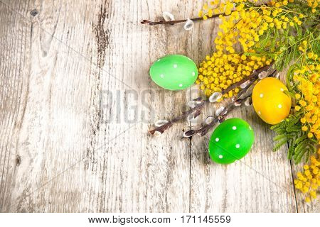 Easter eggs top view spring yellow flowers branch mimosa and willow on old wooden board rustic style. Place for text