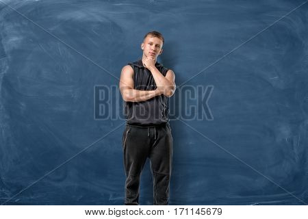 Muscular young man is standing and thinking holding his head with hand on blue chalkboard background. Sport and healthy lifestyle. Keep fit. Athletic body