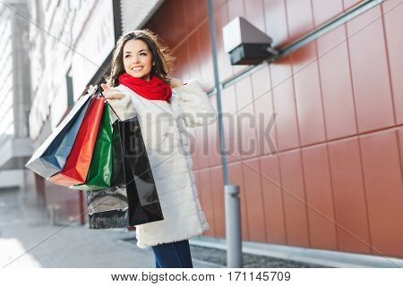 Girl standing with colorful shopping bags near shopping mall and smiling. Beautiful girl with one hand raised holding all bags in it. Wearing white coat, red scarf and jeans. Outdoor