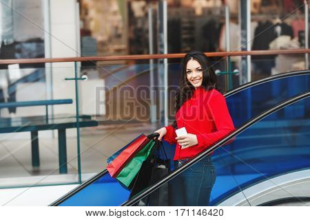 Girl standing on escalator in shopping mall. Beautiful girl holding colorful shopping bags in one hand and phone in other. Woman elbowing on handrail. Wearing red blouse and jeans. Indoor