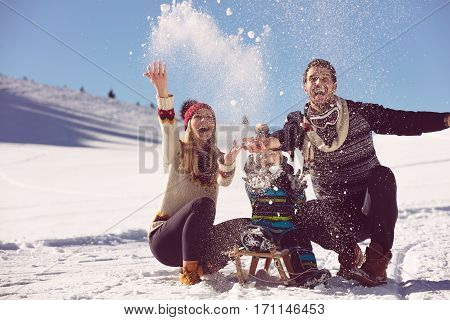 parenthood, fashion, season and people concept - happy family with child on sled walking in winter outdoors.