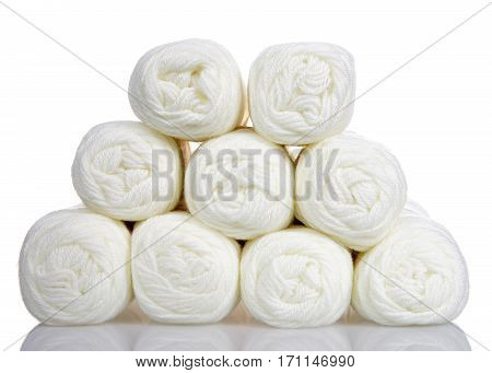 Skeins of off white colored yarn stacked into a pyramid formation on a reflective white surface isolated on a white background.