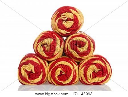 Skeins of red and yellow gold colored yarn stacked into a pyramid formation on a reflective white surface isolated on a white background.